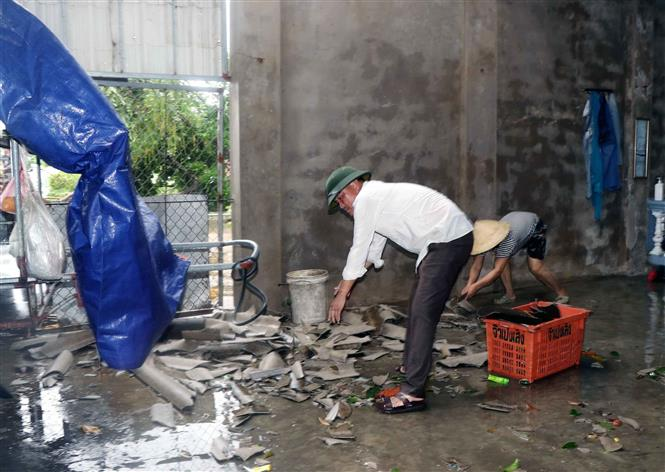 Vợ chồng anh Lê Đình Hùng, thôn Quang Trung xã Thịnh Lộc huyện Lộc Hà đang dọn dẹp mái ngói do lốc xoáy gây ra. Ảnh: Công Tường-TTXVN