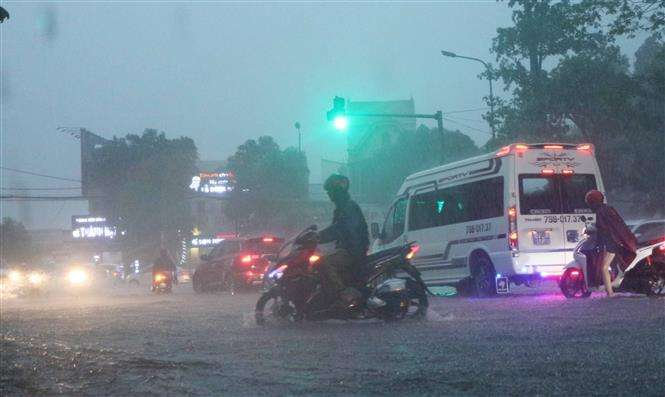 Các phương tiện tham gia giao thông gặp khó khăn do mưa lớn. Ảnh: Nguyễn Oanh-TTXVN.