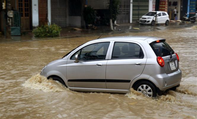 : Ngập cục bộ trên đường Nhạc Sơn, thành phố Lào Cai, khiến các phương tiện tham gia giao thông gặp nhiều khó khăn. Ảnh: Quốc Khánh - TTXVN