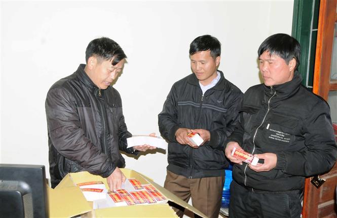 Lãnh đạo xã Lóng Luông phát tem cho đại diện các bản trong xã để cung cấp cho bà con nhân dân dán lên cành đào trước khi bán ra thị trường. Ảnh: Quang Quyết-TTXVN