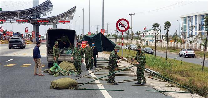 Trong ảnh: Lực lượng chức năng dựng lán chuẩn bị cho công tác phòng chống COVID-19 tại chốt trạm cầu Bạch Đằng, thị xã Quảng Yên. Ảnh: TTXVN
