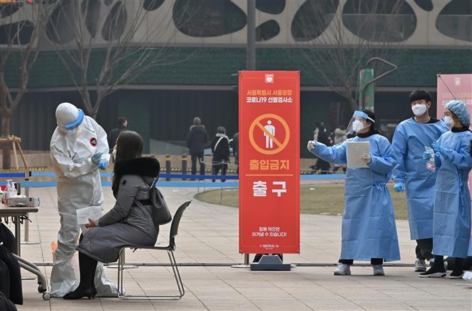 Trong ảnh: Nhân viên y tế lấy mẫu dịch xét nghiệm COVID-19 cho người dân tại Seoul, Hàn Quốc. Ảnh: AFP/ TTXVN