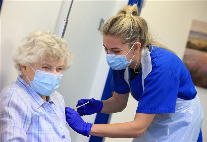 Trong ảnh: Một cụ bà được tiêm vaccine ngừa COVID-19 của Pfizer/BioNTech tại Haxby, Anh ngày 22/12/2020. Ảnh: AFP/TTXVN
