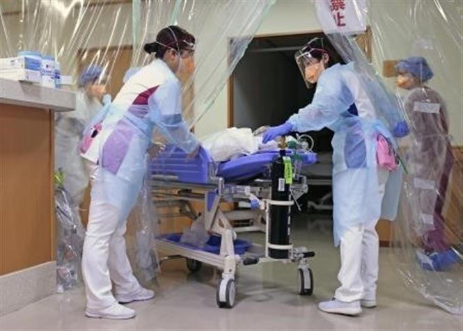 Trong ảnh: Nhân viên y tế chuyển bệnh nhân nhiễm COVID-19 tới bệnh viện ở tỉnh Aichi, Nhật Bản. Ảnh: Kyodo/TTXVN