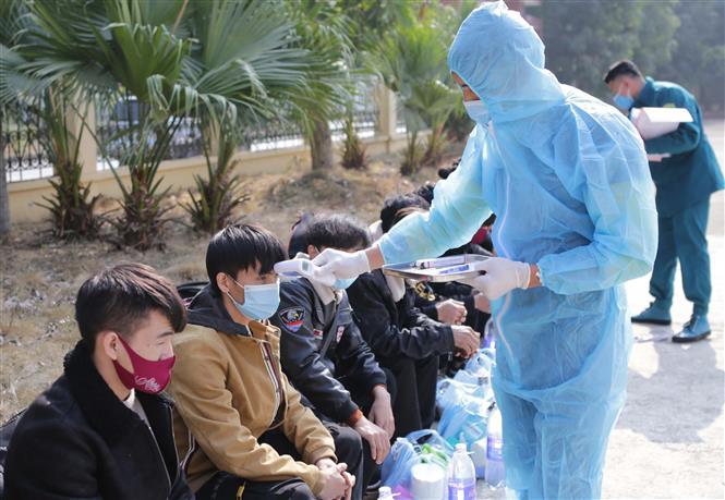 Trong ảnh: Kiểm tra y tế các trường hợp vượt biên trái phép chuẩn bị được đưa đi cách ly nhằm đảm bảo không có sự lây lan dịch bệnh tại khu cách ly cửa khẩu Ma Lù Thàng. Ảnh: Quý Trung - TTXVN