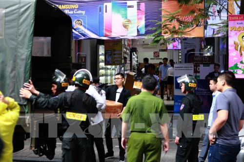 Cảnh sát kiểm tra, khám xét và đưa các kiên hàng lên xe tại của hàng điện thoại Nhật Cường mobile 33 Lý Quốc Sư, Hà Nội ngày 9/5/2019. Ảnh:Doãn Tấn -TTXVn