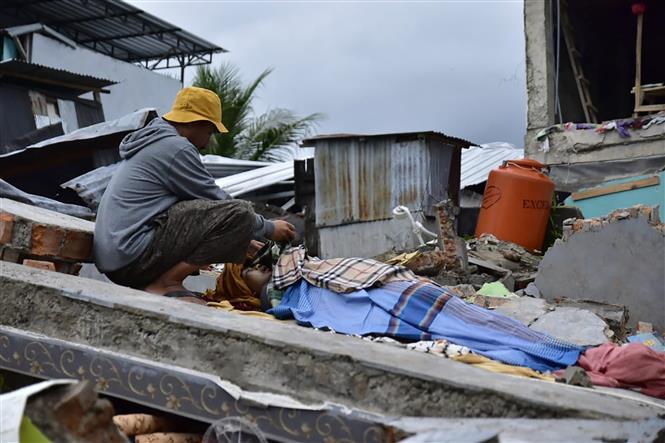 Trong ảnh:Thi thể một nạn nhân thiệt mạng trong trận động đất ở tỉnh Tây Sulawesi , Indonesia, ngày 15/1/2021. Ảnh: AFP/TTXVN
