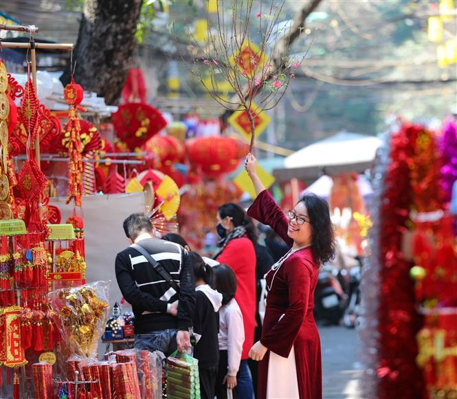 Trong ảnh: Người phụ nữ này tranh thủ bỏ khẩu trang để có bức ảnh đẹp nơi chợ Tết. Ảnh: Thanh Tùng - TTXVN