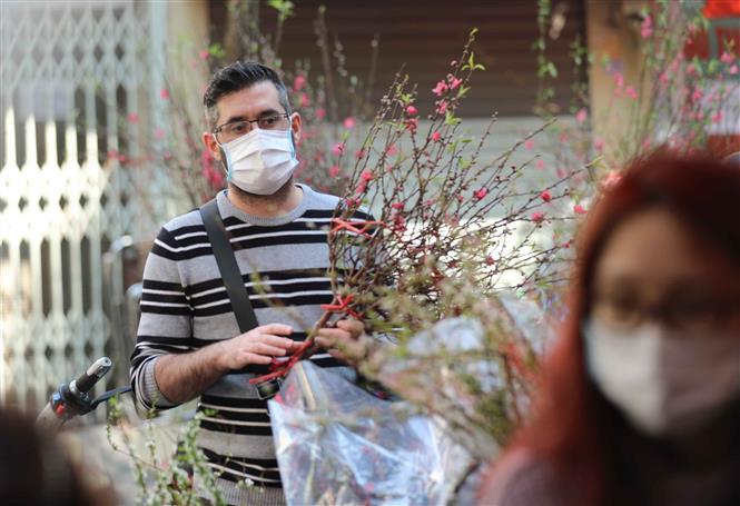 Trong ảnh: Một người nước ngoài đi chợ hoa Tết truyền thống thực hiện nghiêm túc việc đeo khẩu trang để phòng chống dịch. Ảnh: Thanh Tùng - TTXVN