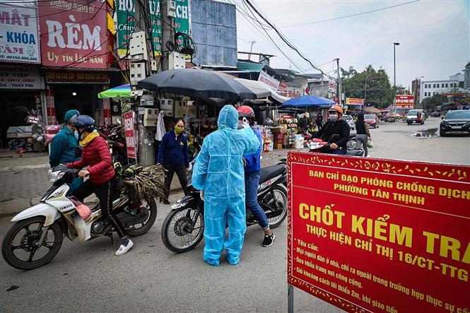 Trong ảnh: Lực lượng chức năng lập chốt thực hiện nghiêm việc đo thân nhiệt, nhắc nhở người dân tuân thủ đeo khẩu trang tại các điểm chợ. Ảnh: Trọng Đạt-TTXVN