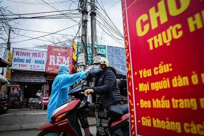 Trong ảnh: Điểm đo thân nhiệt cho người dân trước khi vào chợ ở phường Tân Thịnh, Tp. Hòa Bình. Ảnh: Trọng Đạt-TTXVN