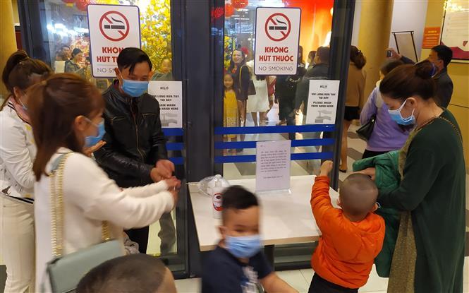 Người dân chủ động thực hiện đeo khẩu trang, xịt sát khuẩn tại các điểm công cộng. Ảnh: Trần Lê Lâm - TTXVN