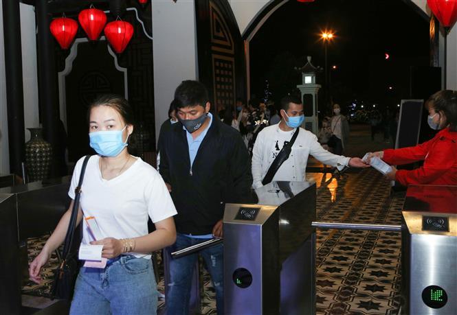 Các tổ kiểm tra xịt sát khuẩn cho người dân tại nơi công cộng. Ảnh: Trần Lê Lâm - TTXVN