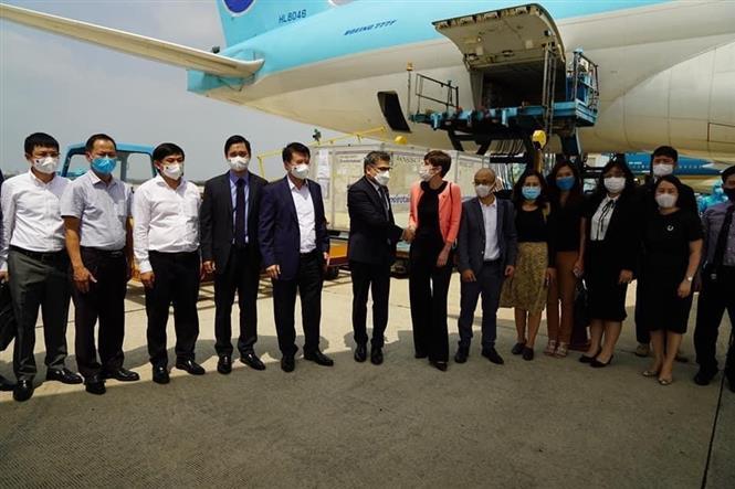 Thứ trưởng Bộ Y tế Trương Quốc Cường tiếp nhận lô vắc xin COVID-19 đầu tiên của AstraZeneca đã về đến Việt Nam. Ảnh: TTXVN phát