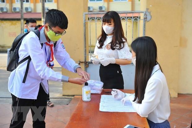 Học sinh sát khuẩn tay trước khi vào trường. (Ảnh: Minh Đức/TTXVN)