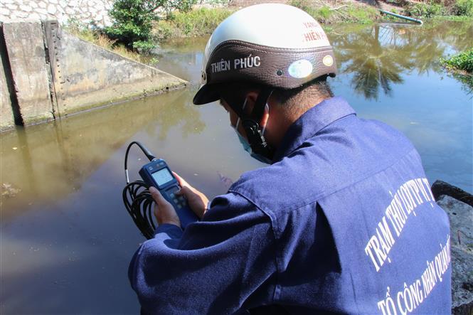Công nhân vận hành cống kiểm tra độ mặn tại cống Kênh Lầu, xã Hỏa Tiến. Ảnh: Hồng Thái - TTXVN