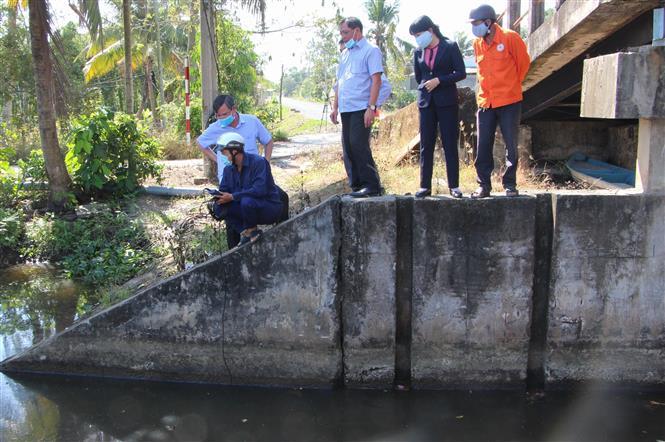 Trong ảnh: Đoàn công tác kiểm tra tình hình xâm nhập mặn tại cống Kênh Lầu, xã Hỏa Tiến. Ảnh: Hồng Thái - TTXVN