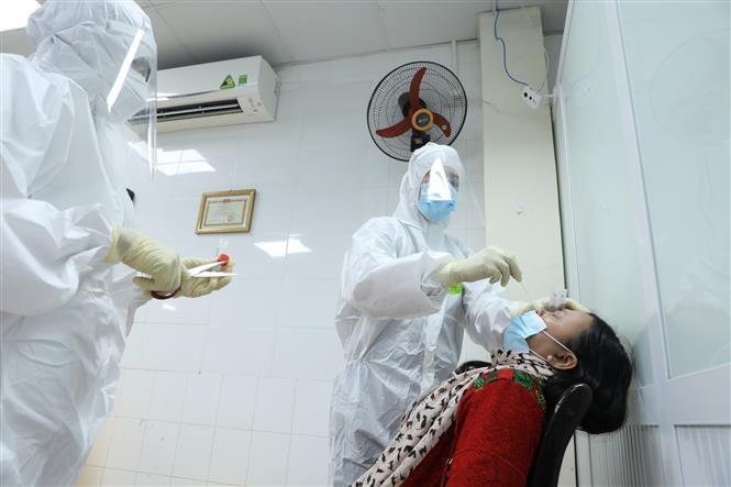 Lấy mẫu xét nghiệm cho tình nguyện viên đăng ký tiêm thử nghiệm giai đoạn 2. Ảnh: Minh Quyết - TTXVN