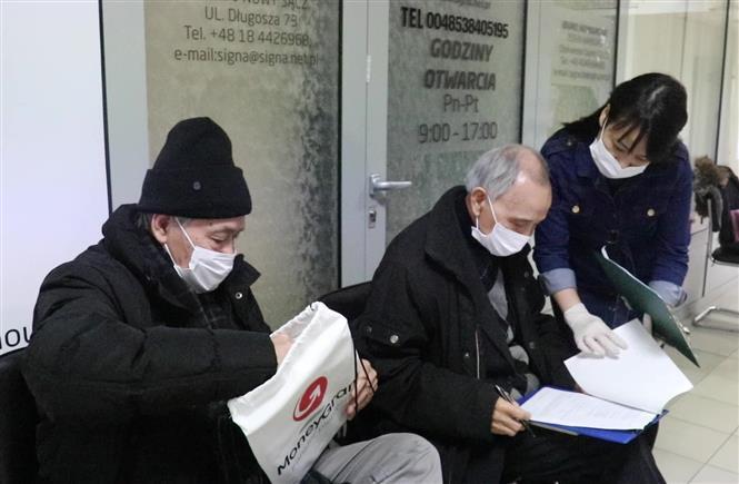 Trong ảnh: Hướng dẫn làm hồ sơ tiêm phòng COVID-19 tại Trung tâm Y tế Lotus, Ba Lan. Ảnh: Văn Long - TTXVN phát