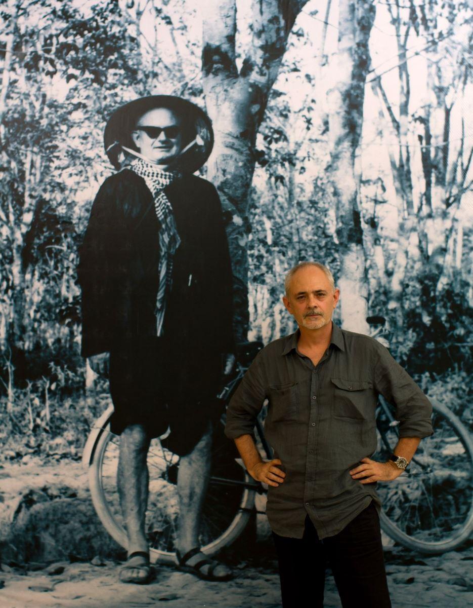 George Burchett  chụp cạnh bức chân dung cha mình – nhà báo Wilfred Burchett- tại Bảo tàng Hồ Chí Minh