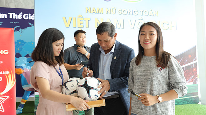 Đội trưởng Huỳnh Như và HLV Mai Đức Chung mỏi tay ký tặng CĐV xếp hàng tại TP.HCM ngày 27-12. Ảnh: NT
