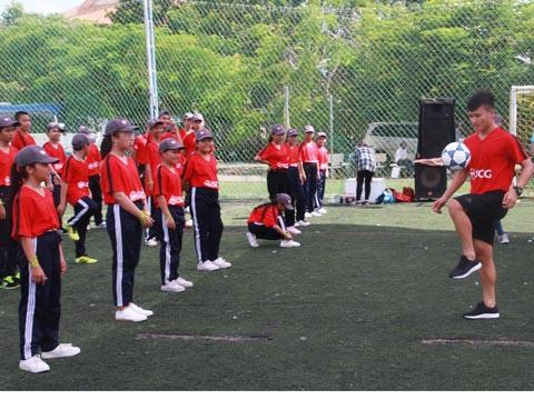 Quang Hải hướng dẫn kỹ năng chơi bóng cho các em thiếu nhi. Ảnh: L.G