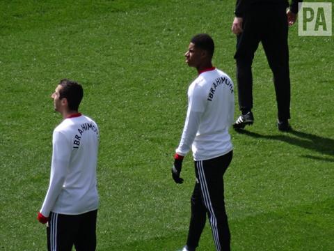 Các cầu thủ Man United mặc áo ghi tên Ibra và Rojo trong lúc khởi động